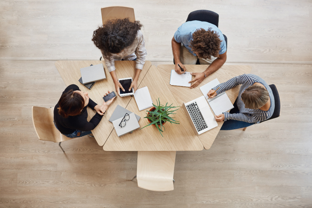 view-from-above-business-startup-teamwork-concept-startup-partners-sitting-at-coworking-space-talking-about-future-project-looking-through-examples-of-work-on-laptop-and-digital-tablet