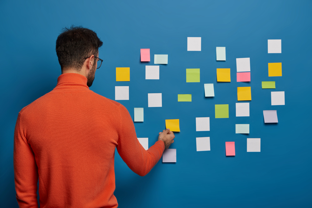 back-view-of-male-professional-works-puts-his-ideas-on-stick-notes-going-to-write-main-info-for-creating-business-plan